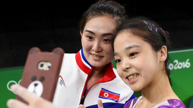 """Algunos dicen que es la foto """"más emblemática de los Juegos"""" y representa como ninguna otra el espíritu olímpico. Lee Eun-ju, de Corea del Sur, y Hong Un-jong, de Corea del Norte, se toman un selfie durante un descanso mientras se entrenaban para las competencias de gimnasia. Ambos países están técnicamente en guerra."""