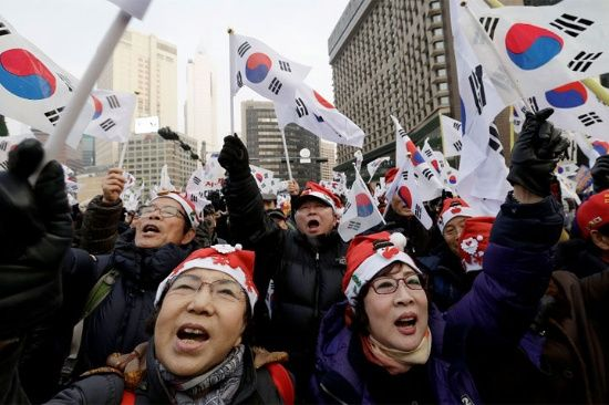Los partidarios del presidente surcoreano Park Geun-hye lanzaron consignas durante una manifestación contra su destitución en Seúl, Corea del Sur. Llevaron gorros de navideños. AP