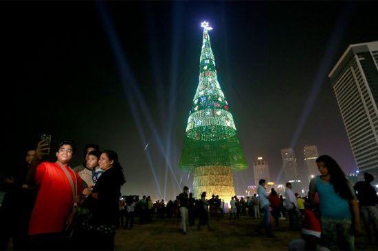 Una familia de Sri Lanka toma fotos de pie cerca de un árbol de Navidad artificial enorme como otros se reúnen alrededor de ella en Colombo, Sri Lanka