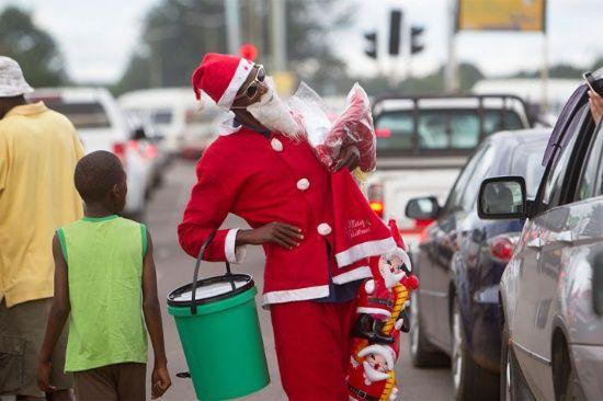 Un automovilista toma una foto de un hombre vestido como Santa Claus en las calles de Harare. La mayoría de las personas en este próspero país de África meridional están luchando para permitirse el lujo de Navidad a medida que la economía implosione.