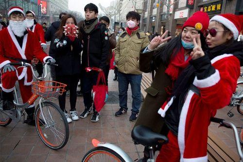 Trabajadores vestidos como Santa Claus promueven el popular servicio de alquiler de bicicletas conocido como Mobike en Beijing, China.