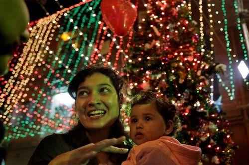 Una madre india con su hijo habla a otro frente a una iglesia decorada en la víspera de Navidad en Kolkata, India. Aunque los hindúes y los musulmanes comprenden la mayoría de la población en la India, la Navidad es celebrada con mucha fanfarria