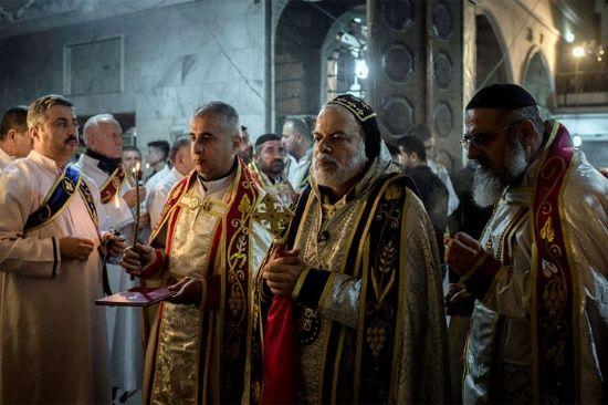 Los sacerdotes dirigen una misa de Navidad en la Iglesia Ortodoxa Asiria de Mart Shmoni, en Bartella, Irak. Unos 300 cristianos se enfrentaron a la lluvia y el viento para asistir a la eucaristía.
